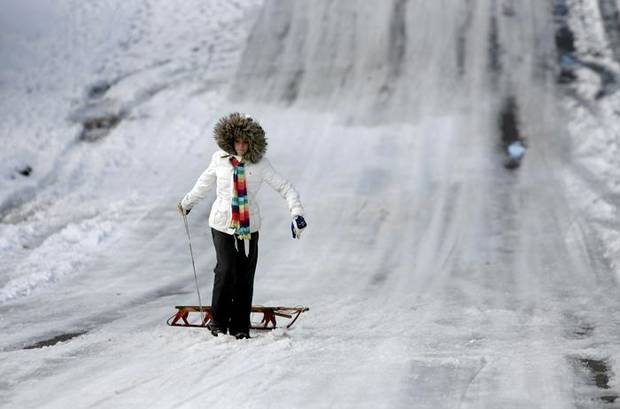 Claire McCoy, 12, pulls her sled up a hill in the Trails neighborhood, Saturday, Dec. 26, 2009, in Edmond, Okla. Photo by Sarah Phipps, The Oklahoman