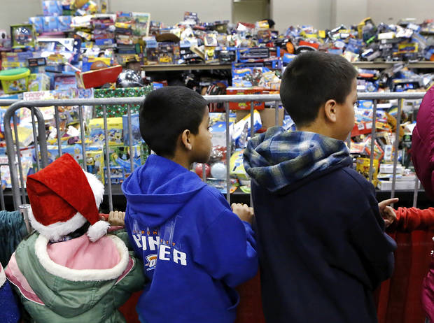 Three children survey hundreds of toys as they wait in a line to see Santa and receive a gift  they get to select. Hundreds were served a traditional Christmas meal at the annual Red Andrews Dinner inside the Cox Convention Center on Christmas Day, Dec. 25, 2012. An army of  volunteers showed up despite  snow and ice and hazardous driving conditions. They accompanied each guest through the serving line and carried their trays and seated them at their tables. Other volunteers distributed a small mountain of toys and stuffed animals that were donated for the event.   Photo by Jim Beckel, The Oklahoman