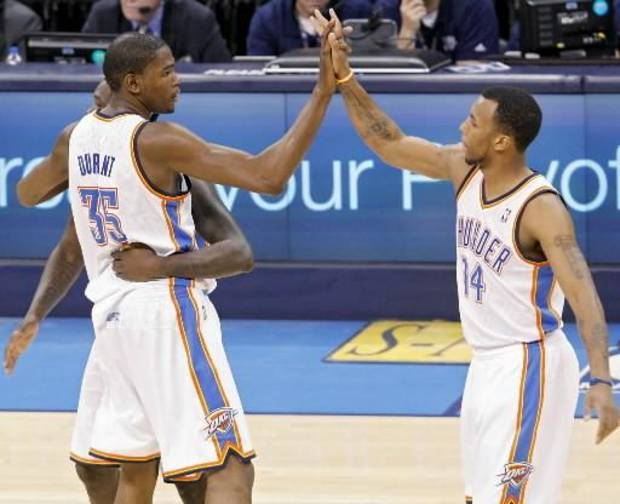 Kevin Durant celebrates with Daequan Cook (right) and Royal Ivey (partially hidden) as Durant leaves the game during the fourth quarter of game 7 of the NBA basketball Western Conference semifinals between the Memphis Grizzlies and the Oklahoma City Thunder at the OKC Arena in Oklahoma City, Sunday, May 15, 2011. The Thunder beat the Grizzlies 105-90 to advance to the Western Conference finals against Dallas. Photo by John Clanton