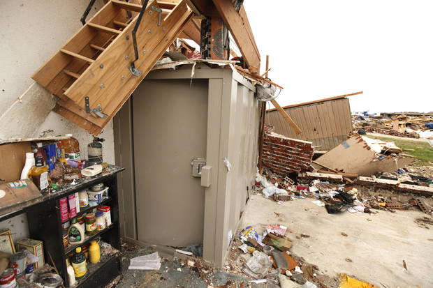 This above ground safe room at a destroyed home on SW 147th St. in Moore, OK, is still standing after taking the impact of May 20th's EF5 tornado. In the background is the remains of Briarwood Elementary School. Thursday, May 30, 2013,  Photo by Paul Hellstern, The Oklahoman