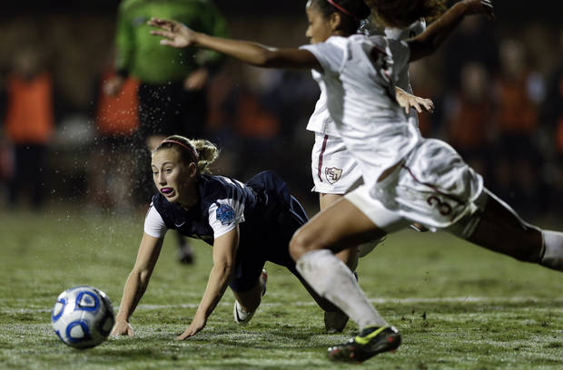 Penn State's Taylor Schram, left, falls as Florida State's Casey Short, right, clears a ball during an NCAA women's college soccer tournament semifinal, Friday, Nov. 30, 2012, in San Diego. (AP Photo/Gregory Bull)