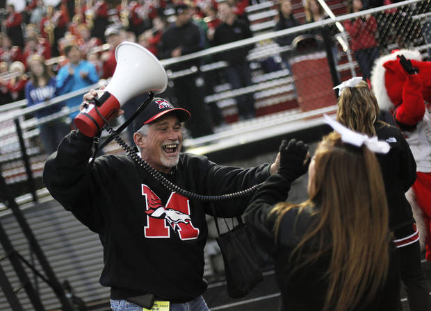 David Baker has cheerleader Brooke McDowell, a senior, scream into a megaphone during a high school football game between Mustang and Stillwater in Mustang, Okla., Friday, Sept. 14, 2012.  Photo by Garett Fisbeck, The Oklahoman
