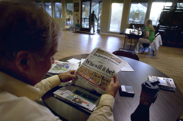Poll manager Michael Blalock reads a newspaper as he waits for voters at his polling site Saturday, Jan. 21, 2012, in Sullivan's Island, S.C. (AP Photo/David Goldman) ORG XMIT: SCDG104