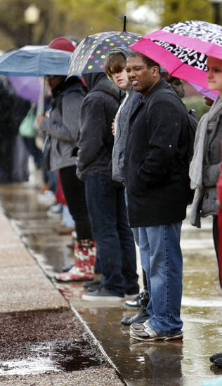 Students wait in the rain for a bus at the University of Oklahoma on Wednesday, April 10, 2013, in Norman, Okla.  Photo by Steve Sisney, The Oklahoman
