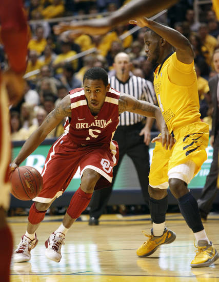Oklahoma's Je'lon Hornbeak, left, drives the ball around West Virginia's Jabarie Hinds during the second half of an NCAA college basketball game against Oklahoma, Saturday, January 5, 2013, in Morgantown, W.Va. (AP Photo/Randy Snyder) ORG XMIT: WVRS105