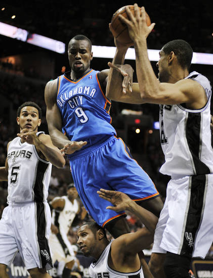 Oklahoma City Thunder's Serge Ibaka (9), of Congo, falls as he chases the ball between San Antonio Spurs' Tim Duncan, right, Boris Diaw, bottom, of France, and Cory Joseph during the second half of an NBA basketball game, Monday, March 11, 2013, in San Antonio. San Antonio won 105-93. (AP Photo/Darren Abate) ORG XMIT: TXDA107