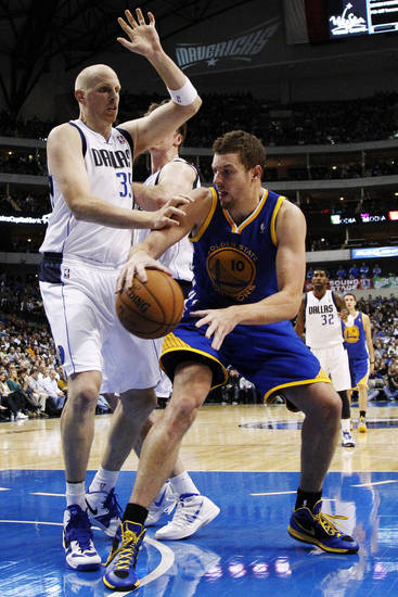 Dallas Mavericks center Chris Kaman (35) guards against a bounce pass by Golden State Warriors' David Lee (10) in the first half of an NBA basketball game, Monday, Nov. 19, 2012, in Dallas. (AP Photo/Tony Gutierrez)