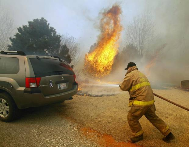 FIREFIGHTERS: A fireman extinguishes a blaze just feet from an automobile on Western Avenue as a large grass fire rages on Friday, March 11, 2011, in Goldsby, Okla. Photo by Steve Sisney, The Oklahoman ORG XMIT: KOD