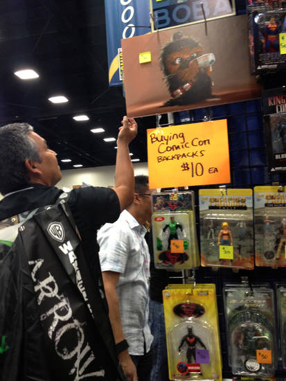 A man examines items for sale at Comic-Con in San Diego Sunday, July 21, 2013.  Comic-Con International and as the four-day   Comic-Con International  winds down Sunday, many vendors in the exhibition hall are cutting prices.   (AP Photo/Matt Moore)