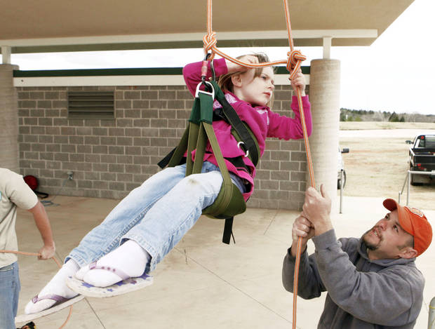 Ivy Webb, 4, learns from arborist Zack Mitchell how to climb trees during Arbor Day festivities at the Multi-Activity Center.  PHOTO BY PAUL HELLSTERN, OKLAHOMAN ARCHIVE