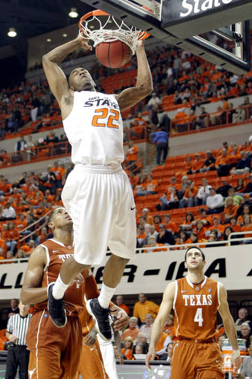 Oklahoma State's Markel Brown (22)�dunks in front Texas' Gary Johnson (1) and Texas' Dogus Balbay (4) during the basketball game between Oklahoma State and Texas, Wednesday, Jan. 26, 2011, at Gallagher-Iba Arena in Stillwater, Okla. Photo by Sarah Phipps, The Oklahoman ORG XMIT: KOD