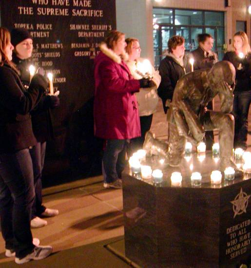 A crowd gathers for a small candlelight vigil  in front of the Law Enforcement Center in Topeka, Kan., Sunday, Dec. 16, 2012. Two Kansas police officers were shot outside a grocery store on Sunday while responding to a report of a suspicious vehicle and died later at a hospital, authorities said. (AP Photo/The Topeka Capital Journal, Corey Jones)