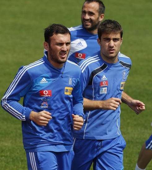 Greece's Vassilis Torosidis, left, and Sokratis Papastathopoulos during a training session at the Euro 2012 soccer championship in Legionowo about 25 kilometers (15 miles) north of Warsaw, Poland on Monday, June 18, 2012. (AP Photo/Thanassis Stavrakis)
