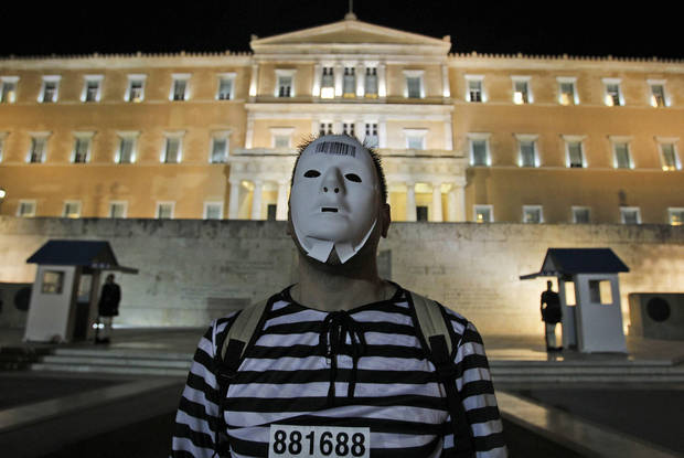 Protesters, dressed as prisoners gather during an event to protest against austerity measures outside the Greek parliament in Athens, Tuesday, Nov. 1, 2011. Lawmakers in Greece's ruling Socialist party revolted Tuesday over their prime minister's surprise decision to hold a referendum on a European debt deal, threatening the very survival of his embattled government. (AP Photo/Thanassis Stavrakis) ORG XMIT: XTS113