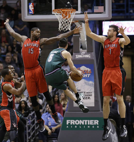 Milwaukee Bucks' J.J. Redick (5) drives against Toronto Raptors' Amir Johnson (15) and Andrea Bargnani (7) during the first half of an NBA basketball game Saturday, March 2, 2013, in Milwaukee. (AP Photo/Jeffrey Phelps)