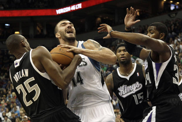 Sacramento Kings' Travis Outlaw, left, tries to wrestle the ball away from Minnesota Timberwolves' Nikola Pekovic of Montenegro as he is surrounded by Kings players including Jason Thompson, right, and DeMarcus Cousins (15) in the first half of an NBA basketball game Friday, Nov. 2, 2012 in Minneapolis. (AP Photo/Jim Mone)