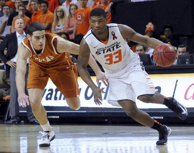 Texas forward Ioannis Papapetrou, left, chases Oklahoma State guard Marcus Smart during the second half of an NCAA college basketball game in Stillwater, Okla., Saturday, March 2, 2013. Oklahoma State won 78-65. (AP Photo/Brody Schmidt)