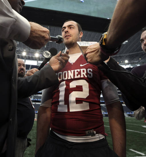 Oklahoma quarterback Landry Jones (12) speaks to reporters during media day for the Cotton Bowl NCAA college football game at Cowboys Stadium, Sunday, Dec. 30, 2012, in Arlington, Texas. Oklahoma is scheduled to play Texas A&M on Jan. 4, 2013. (AP Photo/LM Otero) ORG XMIT: TXMO106