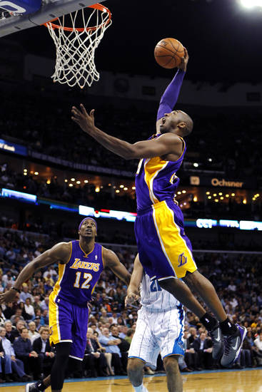 Los Angeles Lakers guard Kobe Bryant (24) drives to the basket in front of center Dwight Howard (12) and New Orleans Hornets guard Greivis Vasquez (21) in the first half of an NBA basketball game in New Orleans, Wednesday, Dec. 5, 2012. (AP Photo/Gerald Herbert)