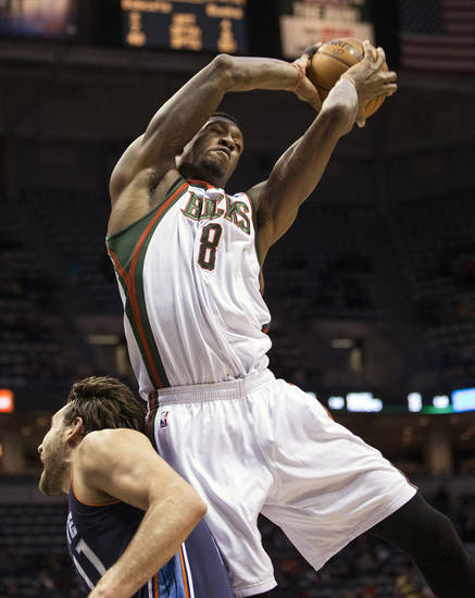 Milwaukee Bucks' Larry Sanders, right,  grabs a rebound over Charlotte Bobcats' Josh McRoberts during the first half of an NBA basketball game Monday, April 1, 2013, in Milwaukee. (AP Photo/Tom Lynn)