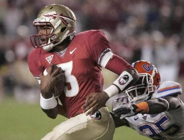 Florida State University's EJ Manuel out runs Florida's Ahmad Black for a first down in the fourth quarter of an NCAA college football game which Florida State won 31-7 on Saturday, Nov. 27, 2010, in Tallahassee, Fla.(AP Photo/Steve Cannon)