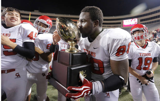 Carl Albert's Chantz Woodberry (80) kisses the trophy while celebrating the win over East Central during the Class 5A Oklahoma state championship football game between Carl Albert High School and Tulsa East Central High School at Boone Pickens Stadium on Saturday, Dec. 1, 2012, in Stillwater, Okla.   Photo by Chris Landsberger, The Oklahoman