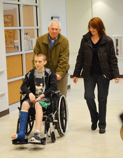 Phil and Shelley Smith walk with their son, Luke, who was injured last month in a �car surfing� incident in Edmond. PHOTO PROVIDED