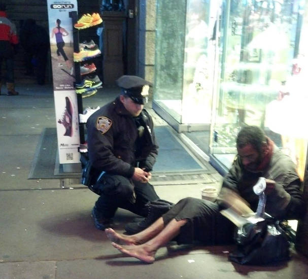 This photo provided by Jennifer Foster shows New York City Police Officer Larry DePrimo presenting a barefoot homeless man in New York&#039;s Time Square with boots Nov. 14, 2012 . Foster was visiting New York with her boyfriend on Nov. 14, when she came across the shoeless man asking for change in Times Square. As she was about to approach him, she said the officer  came up to the man with a pair of all-weather boots and thermal socks on the frigid night. She took the picture on her cellphone. It was posted Tuesday night to the NYPD&#039;s official Facebook page and became an instant hit. More than 350,000 users &quot;liked&quot; it as of Thursday afternoon, and over 100,000 shared it. (AP Photo/Jennifer Foster)