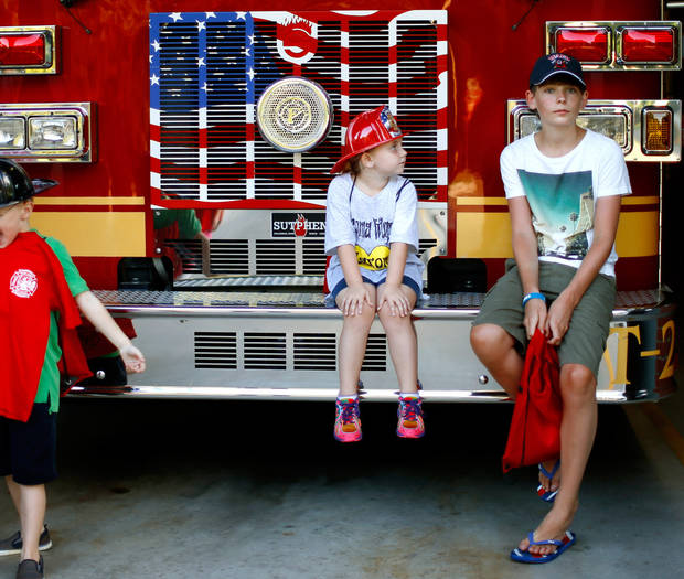 Cancer patient Sam Oliver, 13, from London, sits beside Peyton Dugger, 6, from Hollis, Okla., as they wait for a group photo on a Warr Acres fire truck, Wednesday, July 24, 2013. Peyton is caner patient Jaxon Dugger's sister. Photo by Bryan Terry, The Oklahoman