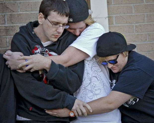 Daniel Flynn, Stephanie Spehar and Anna Sandoval, from left, hug each other  as they gather during a vigil on Tuesday afternoon for Carina Saunders, whose body was found in a duffel bag last week behind a Bethany Homeland last week. <strong>CHRIS LANDSBERGER - CHRIS LANDSBERGER</strong>
