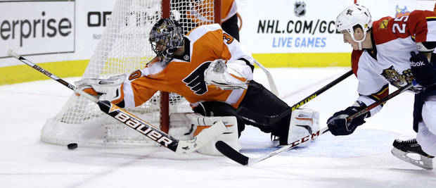 Philadelphia Flyers goalie Ilya Bryzgalov, left, of Russia, dives to cover up the puck as Florida Panthers' Jerred Smithson looks for the rebound during the first period of an NHL hockey game, Thursday, Feb. 7, 2013, in Philadelphia. (AP Photo/Matt Slocum)