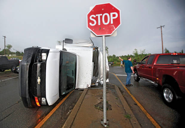 Left: A truck lays on its side Monday near Interstate 240 and Choctaw Road in Oklahoma City.  Photo by  Chris Landsberger,  The Oklahoman
