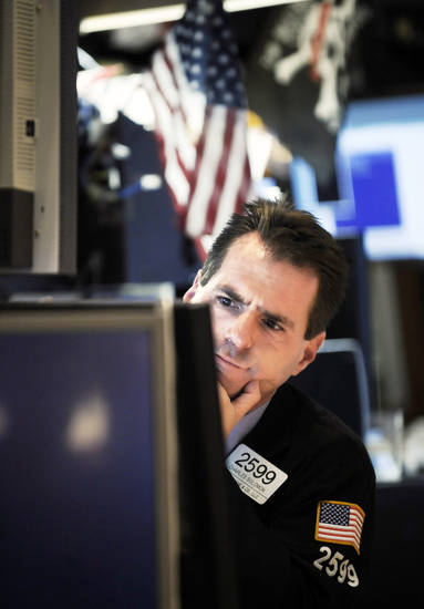 Specialist Charles Solomon works at his post Wednesday on the floor of the New York Stock Exchange. A case of postelection nerves sent Wall Street plunging Wednesday as investors absorbing a stream of bad economic news wondered how a Barack Obama presidency will help the country weather a possibly severe recession. AP PHOTO