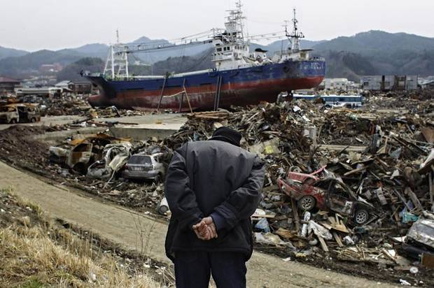 An eldery Japanese man observes the area devastated by the March 11 earthquake and tsunami in the port town of Kesennuma, Miyagi prefecture, Japan, on Monday, April 11, 2011.  Exactly a month ago today a massive earthquake and tsunami ravaged Japan's northeastern coastal region. (AP Photo/Sergey Ponomarev) ORG XMIT: XSP103