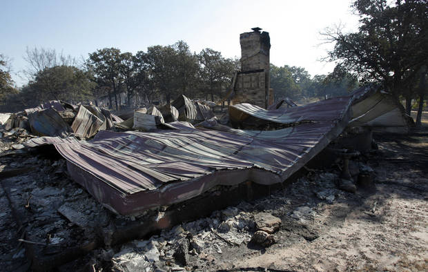 The remains of Ricky Oliver and his mother Rosalee Oliver's home on 132nd Street  still smolders from Friday's wildfire on Saturday, Aug. 4, 2012, in Slaughterville, Okla.  They were evacuated as the fire approached.  Photo by Steve Sisney, The Oklahoman