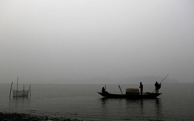 Indian fishermen row a boat on a cold evening in the River Brahmaputra in Gauhati, India, Tuesday, Jan. 8, 2013. North India continues to face below average weather conditions with dense fog affecting flights and trains. (AP Photo/Anupam Nath)