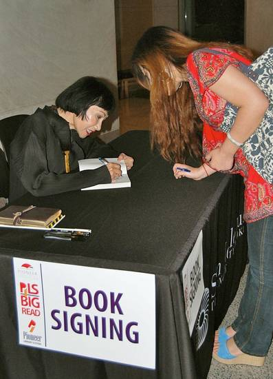 Author Amy Tan signs a copy of �The Joy Luck Club� for OU student Hui Cao after a speech at the Sam Noble Oklahoma Museum of Natural History. PHOTO BY ANNETTE PRICE, For The Oklahoman