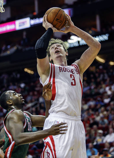 Houston Rockets center Omer Asik (3) is fouled by Milwaukee Bucks forward Luc Richard Mbah a Moute (12) during the second half of an NBA basketball game, Wednesday, Feb. 27, 2013 in Houston. Milwaukee won 110-107. (AP Photo/Bob Levey)