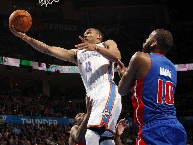 Oklahoma City's Russell Westbrook (0) takes the ball to the hoop between Brandon Knight (7) and Greg Monroe (10) of Detroit during the NBA basketball game between the Detroit Pistons and Oklahoma City Thunder at the Chesapeake Energy Arena in Oklahoma City, Monday, Jan. 23, 2012. Photo by Nate Billings, The Oklahoman