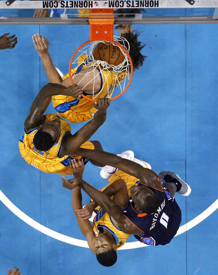 New Orleans Hornets small forward Al-Farouq Aminu slam dunks onto center Robin Lopez (15) as power forward Anthony Davis, bottom left, blocks out Charlotte Bobcats point guard Cory Higgins (11) in the first half of an NBA basketball game in New Orleans, Friday, Nov. 9, 2012. (AP Photo/Gerald Herbert)