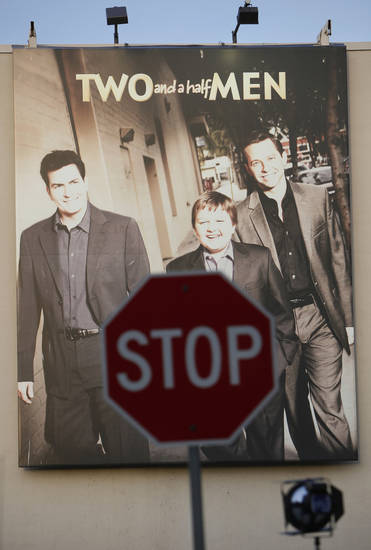 "A banner for  the hit sitcom ""Two and a Half Men"" is seen at the Warner Bros. studios in Burbank, Calif. Monday, March 7, 2011. Warner Bros. television said it has fired actor Charlie Sheen from the hit sitcom. The studio that produces the CBS series said the decision was made after ""careful consideration.""  (AP Photo/Damian Dovarganes)"