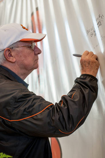 "Tom Ikard signs the  ""Remember the 4"" banner Friday in Gallagher-Iba Arena in Stillwater. Photo by Mitchell Alcala for The Okahoman <strong>Mitchell Alcala - Mitchell Alcala for the Oklahoma</strong>"