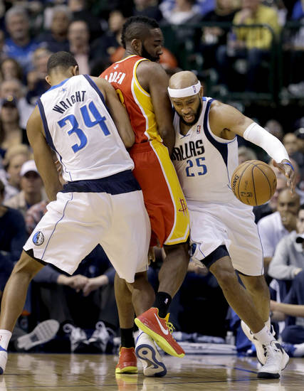 Dallas Mavericks' Brandan Wright (34) sets the pick as Vince Carter (25) gets around Houston Rockets' James Harden, center, in the first half of an NBA basketball game, Wednesday, March 6, 2013, in Dallas. (AP Photo/Tony Gutierrez)