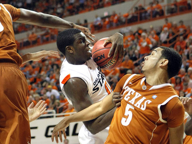 Oklahoma State's Jean-Paul Olukemi (0) grabs a rebound in front of Texas' Cory Joseph (5) during the basketball game between Oklahoma State and Texas, Wednesday, Jan. 26, 2011, at Gallagher-Iba Arena in Stillwater, Okla. Photo by Sarah Phipps, The Oklahoman ORG XMIT: KOD