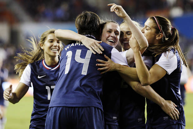United States' Abby Wambach (14) celebrates with teammates after scoring a goal during the first half of an exhibition soccer match against China, Wednesday, Dec. 12, 2012, in Houston. (AP Photo/David J. Phillip)
