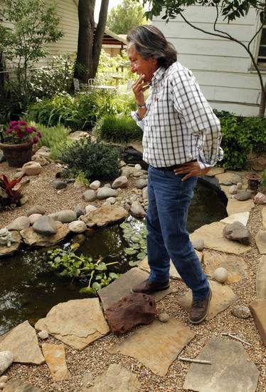 Indian artist and poet Joe Dale Tate Nevaquaya walks through a garden in the backyard of his Norman home. PHOTO BY STEVE SISNEY, THE OKLAHOMAN <strong>STEVE SISNEY - THE OKLAHOMAN</strong>