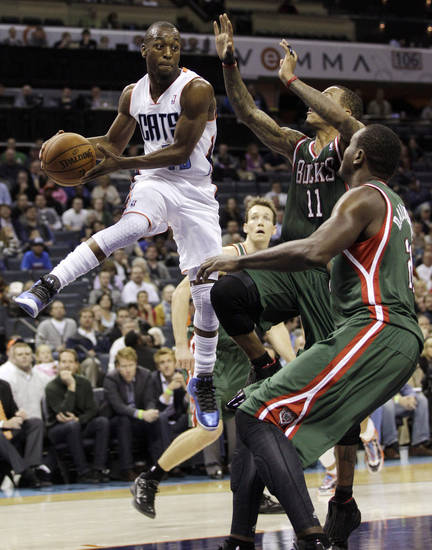 Charlotte Bobcats' Kemba Walker, left, looks to pass as Milwaukee Bucks' Monta Ellis, center, and Samuel Dalembert, right, defend during the first half of an NBA basketball game in Charlotte, N.C., Monday, Nov. 19, 2012. (AP Photo/Chuck Burton)