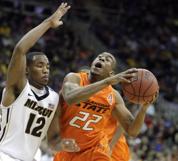 Oklahoma's Markel Brown (22) shoots as Missouri's Marcus Denmon (12) defends during the Big 12 tournament men's basketball game between the Oklahoma State Cowboys and Missouri Tigers the Sprint Center, Thursday, March 8, 2012. Photo by Sarah Phipps, The Oklahoman