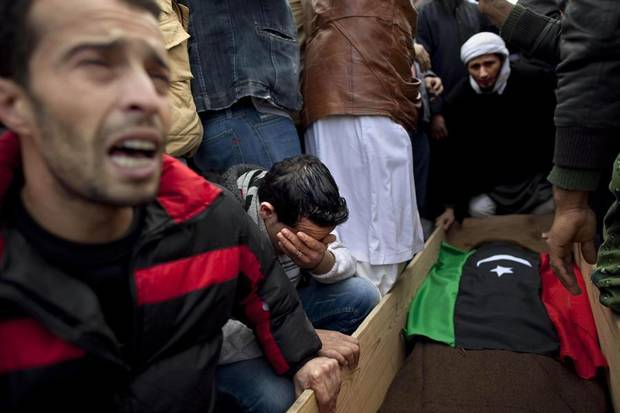 ORG XMIT: AKCF104 Mourners react next to the coffin during the funeral for a rebel fighter who was killed fighting forces loyal to Libyan leader Moammar Gadhafi near the town of Bin Jawwad, during his funeral in Benghazi, eastern Libya, Wednesday, March 9, 2011. (AP Photo/Kevin Frayer)