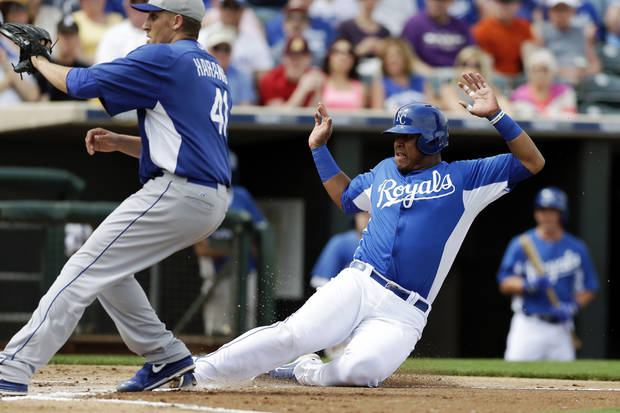 Kansas City Royals' Salvador Perez, right, slides in safely to home as Los Angeles Dodgers starting pitcher Aaron Harang, left, waits for the throw from catcher Tim Federowicz after Harang threw a wild pitch during the first inning in an exhibition spring training baseball game Wednesday, March 20, 2013, in Surprise, Ariz. (AP Photo/Gregory Bull)